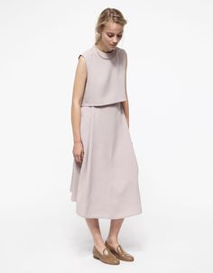 Deep pleated midi skirt from Kaarem. Features back zip and clasp closure, textured feel, and an easy overlapping pleated front.   •Deep pleated midi skirt •Textured feel •Back zip and clasp closure •100% Polyester •Hand wash cold, air dry