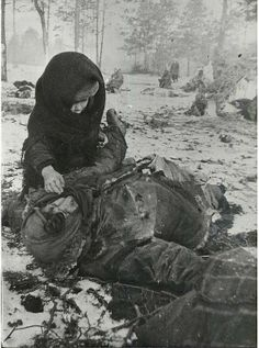 A little Russian girl touches her dead mother, in the concentration camp Ozarichi right after the liberation. 1944