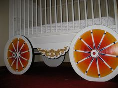 paint a round pieces of wood as wheels and put it in to the crib!! so cute for circus nurseries