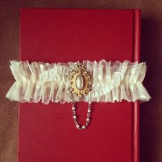 Vintage Pearl Gold Rhinestone Medallion with Pearl Swag, French Ivory Lace, Point dEsprit and Tulle Bridal Garter. $62.00, via Etsy.
