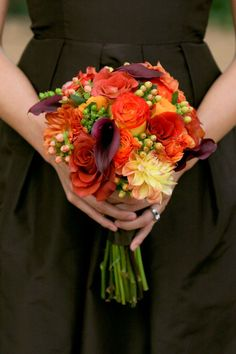 Fall Bridesmaid.  Orange ranuculus, calla lilies, dahilas, roses make up a fall posey