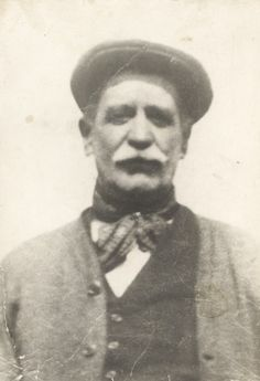 Head and shoulders portrait of an elderly boatman wearing a flat cap, neckerchief, waistcoat, collarless shirt and a jacket. Early 20th century.