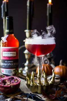 Red Vampire's Venom Cocktail with dry ice smoke bubbling in a gold skeleton hand with candles and cocktail bottle in background. Cocktail Drinks, Cocktail Recipes, Fancy Drinks, Drink Recipes, Refreshing Drinks, Yummy Drinks, Halloween Cocktails, Halloween Party, Holiday Drinks