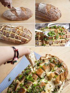 Cortar el pan sin llegar al fondo, rociar con una mezcla de mantequilla de ajo y cebolla picaditas introduciéndola en los cortes ayudados de una cucharilla, rellenar los cortes con lonchas de queso o queso rallado. Envolver en papel de aluminio y hornear 15 minutos, retirar el papel y hornear 10 minutos más.