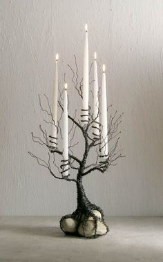 Start by cutting around 50 lengths of wire, and begin wrapping the edges of a few pieces of wire around the base of a candle to form a spiral that will hold the candle in place. Make as many spirals as you like depending on how many candles you would like your tree to hold. Twist the remaining pieces of wire together to form tree branches, and then wrap all the wires together to form your tree trunk leaving around three or four inches at the end to make the tree roots.