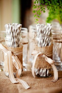 Mason jars wrapped with burlap and brown ribbon to hold straws.  Rustic wedding
