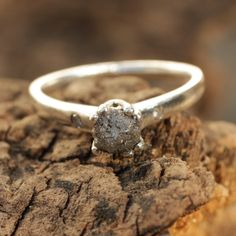 Silver ring with prong set rough diamond and side set pave diamonds
