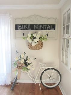 A vintage bike with her basket all decked out, and you just have to love the chalkboard sign (from an old headboard?) hanging above her.  Way too cute!