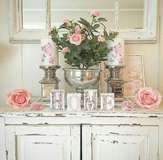 Beautiful peachy pink roses and candles on a shabby chic chippy cabinet.