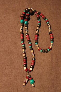 Necklace with brown & turquoise wood beads, natural coconut wood rondelles , red wood Abacus rondelles, red Yak bones, red agate beads, green skulls & white boddhi seeds. 40 €