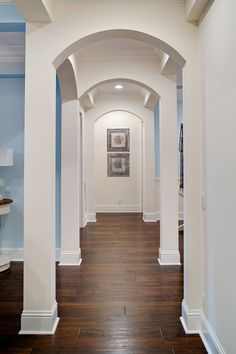 Amazing corridor. Dark hardwood floors. Whitwe trim. Blue walls. House of Turquoise.
