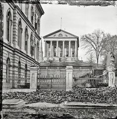 "April 1865. ""Fallen Richmond -- Custom House (left) and Virginia State Capitol; rubble in street."" Wet plate glass negative."
