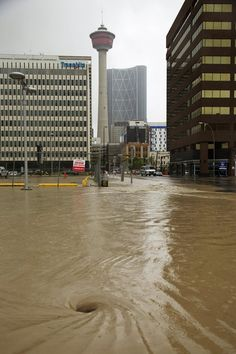 A police van patrols as floodwaters rise at a downtown street during a mandatory evacuation in Calgary, The Province, Wild West, Pretty Cool, Calgary, Seattle Skyline, Police, Places To Visit, Canada