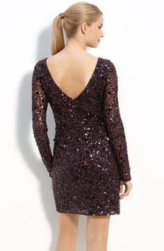 A smattering of sequins and paillettes catch the light on a sheath dress with long, sheer sleeves.