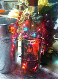 Carmela Winerita lighted bottle with potpourri inside. This bottle will never be seen again since the vineyard changed its name. It is accented with grapes, vines and leaves with ribbon. It was also paired with a steel wine holder and a bottle of Crossings new wine.