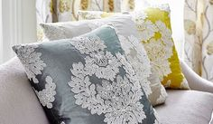 James Hare -  Portobello Fabric Collection - A large, ornate white pattern appliquéd onto silver-blue, pale grey and mustard coloured cushions, on a plain white sofa