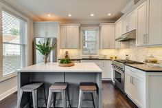 Contemporary Kitchen with Hardwood floors, Slate counters, Flush, Complex Marble Tile, Kitchen island, Travertine Subway Tile