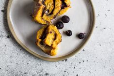 Fluffy sweet potato brioche-style dough is swirled with cinnamon sugar and dotted with jammy blueberries in this vegan cinnamon roll recipe.