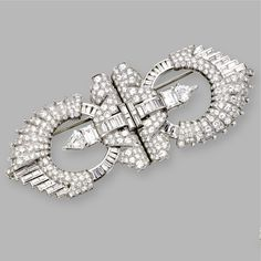 DIAMOND DOUBLE-CLIP/BROOCH, CIRCA 1930 The modified lozenge-shaped brooch separating into a pair of shield-shaped clips, set with 2 kite-shaped, 2 emerald-cut, 60 baguette and numerous round diamonds weighing a total of approximately 21.60 carats, mounted in platinum.
