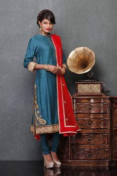 Redefine elegance with this stunning bandhgala kurti, fashioned in raw silk and lycra net. This designer piece is rendered with amazing thread work on turquoise blue base, to create beautiful embellished patterns. It is paired with a sultry red dupatta showcasing stunningly beautiful embellishments and a simple churidaar to compliment the ensemble; $819; really expensive though colors are perfect