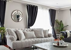 Large lounge room with all around windows - a linen 3.5 seater sofa on one side and another navy fabric chesterfield at the other corner, sitting on a patterned oversized rug and bone inlay coffee tables.    #curtain #loungeseat #tablestyling #decoration #planter #shellsculpture #cushion #mirror #reflection #hangingplants #greenery