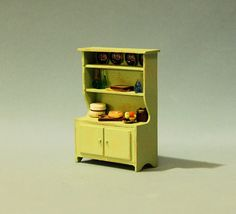 This is a decorated hutch in 1/4 inch scale. The hutch is laser cut and painted light green. The hutch is painted and slightly distressed to show wear. Included with the hutch are dishes, wine bottles, bowls, cutting boards, 1 bowl of fruit, and 1 cake. The hutch is 1 7/8 inches tall.  The hutch is made by sdk miniatures LLC.  The items in our etsy store are NOT childrens toys. They are adult collectibles and unsuitable for children under 14 years of age.