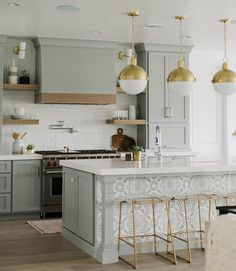 Beautiful kitchen with soft grey cabinets and gold accents.