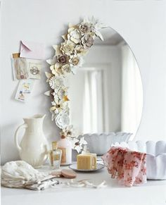 Hot glue embellishments like fake flowers to a plain mirror