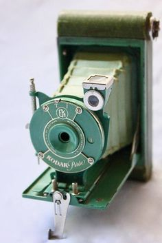 Kodak Petite is a green colored Vest Pocket Kodak Model B camera and was made from 1929 to 1934. The Kodak Petite cameras came in five colors: blue, green, gray, lavender and old rose, with matching colored bellows. The body covering has a diamond patterning. It has the Autographic back with a stylus on the front lens mount and used 127 roll film.