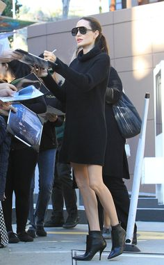 Angelina Jolie signs autographs while donning a chic all-black ensemble and flat-top modified aviator shades.