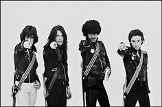 Thin Lizzy pose for a group portrait, pointing at the camera, on the set of the 'Do Anything You Want To Do' music video, London, 1979. Left to right: Gary Moore, Scott Gorham, Phil Lynott and Brian Downey.