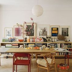 Dining room with low bookcase, vintage art, mismatched chairs