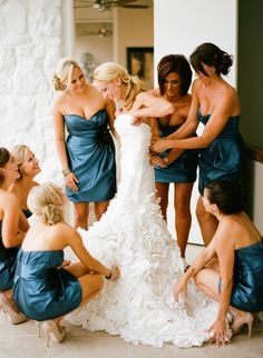 bridesmaids helping bride get dressed.  CUTE