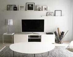 Tauluhyllyt television yläpuolella tuovat vaihtuvan taidenäyttelyn olohuoneeseen.