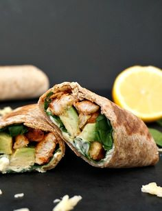 Grilled chicken avocado wrap halves with a lemon wedge next to it and grated cheese scattered around
