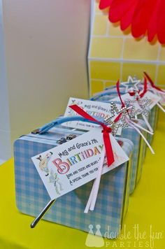 """Party decorations could include: Miss Gulch's bicycle, the Witch's hourglass, Dorothy's suitcase, and bluebirds. Backdrop of blue gingham (and rick rack on place mats) or a print of """"Somewhere Over the Rainbow"""" (from Sugar Fresh on etsy.) Take home favor gift of Gingham tin lunch box - inside, each box had rainbow bubbles, heart necklace, rainbow hair elastics and a Glinda wand."""
