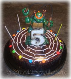 Teenage Mutant Ninja Turtles Cake: Spruce up a store bought cake with a child's favorite figurine/toy and some Smarties. Cost about $7.