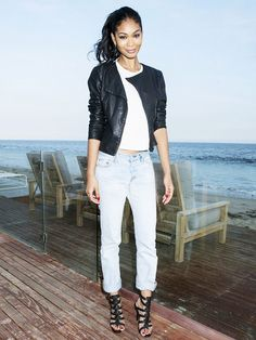 Chanel Iman poses in a white crop top, black leather jacket, boyfriend jeans and black gladiator heels.
