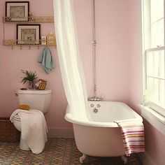 Pretty pink walls give any bathroom a serene feel -- but huge windows, a potted plant and freestanding clawfooted vintage bathtub make this one especially charming. Find your perfect pink paint color here on our Style Guide!