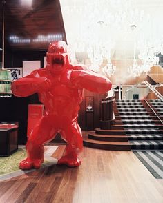 French Contemporary Entry: A red gorilla sculpture at the base of a mirrored stairwell.