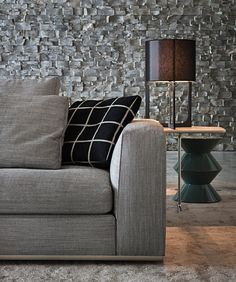 Living Room - The off set stone textured walls, gray linen sofa with a mix of accent pillows plus adding a glossy black lathed side table brings this contemporary space to the fore front in clever design.  (re-pinned photo only from Minotti)