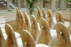 Ivory chair cover with gold organza sash and ivory rose tieback decoration - Pumpkin Events Ltd