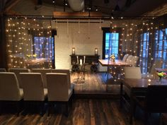 A beautiful ceremony set up with cascade twinkle lights to frame the couple for a lovely spring wedding at Virtue Feed & Grain #virtueevents #rusticweddings #simpleeleganceTheir theme was 'wood & lights' with dashes of colorful flowers in mason jars on the tables - so pretty!