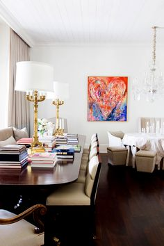Living room with white walls, beige curtains, colorful artwork, dark wood floors, wood dining table, beige chairs, large gold and white lamps, crystal chandelier, and an assortment of books