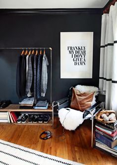 Teen bedroom with leather, dark colors, and a rustic clothes rack.
