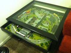 Liatorp coffee table with glass top and pull out drawer that was modified to include an N scale model train set.