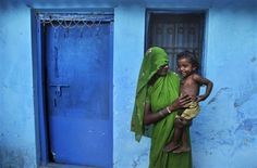 An Indian woman holds her child outside her house in Allahabad, India, May 13. (Rajesh Kumar Singh / AP)