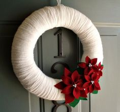 Beautiful way to welcome the holiday season!  This wreath is wrapped in a snow white yarn with a cluster of poinsettia flowers and leaves.. perfect for