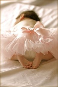 An adorable newborn photograph of a baby girl wearing a soft pink tutu with a girly bow and her little bare feet tucked under her.