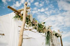 floral garland and sheer white curtains on ceremony arch